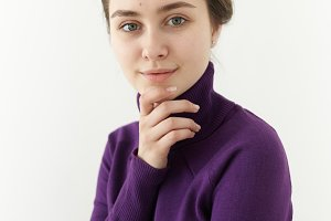 People and lifestyle concept. Picture of positive stylish woman in her twenties dressed in cozy cashmere turtle neck touching chin and smiling joyfully at camera. Cute girl posing in studio