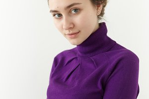 Vertical shot of charming young Caucasian female with gathered hair, clean perfect skin and blue eyes posing isolated against white studio wall background, wearing trendy violet turtle neck