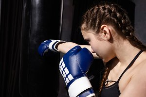Sideways shot of concentrated 14 year old Caucasian girl with braids wearing black sports bra and blue boxing gloves standing at punch bag, mastering punching technique during training in gym