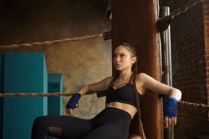 Picture of serious young professional female kickboxer wearing trendy sports outfit and bandages on her hands, having rest after training, sitting comfortably on chair in the corner of boxing ring
