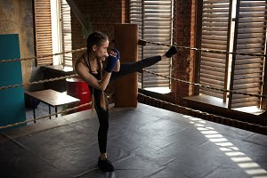 Full length shot of stylish young woman athlete in black sportswear standing in boxing ring, lifting one leg, doing high kick, fighting against invisible enemy. Sports, martial arts and kickboxing