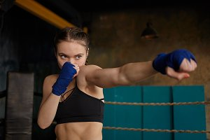Cropped portrait of self determined young woman professional boxer with strong muscular arms and abdominal wearing black sports top and blue boxing bandages mastering punching technique in gym