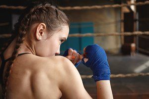 Sideways view of athletic young woman with two braids and muscular back wearing handwraps standing in defensive stance, holding hands in front of her, focused on punches during boxing training in gym