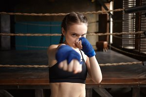 Self defense, fitness and sports concept. Serious determined young female with braids wearing sports bra and boxing handwraps reaching out hand at camera as if punching you. Selective focus