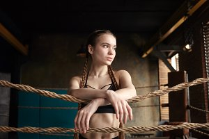 Picture of attractive muscular young Caucasian female posing indoors in boxing ring, having rest after intensive workout, placing hands on rope and looking sideways with serious facial expression