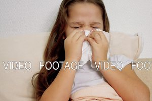 ill girl with paper tissue on the bed