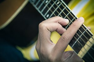 man's hands playing acoustic guitar