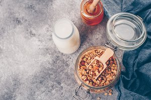 Homemade granola in glass jar on gra