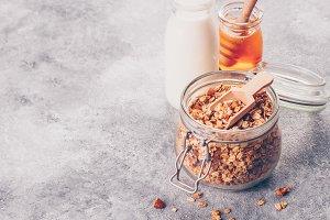 Homemade granola in glass jar on gra