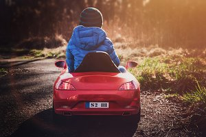 Boy driving red toy car