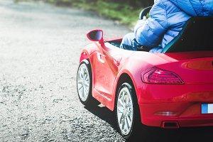 Boy inside red toy car