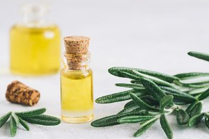 Rosemary essential oil in small glass bottle fresh rosemary