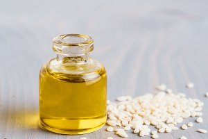 Bottle of sesame oil and sesame seeds
