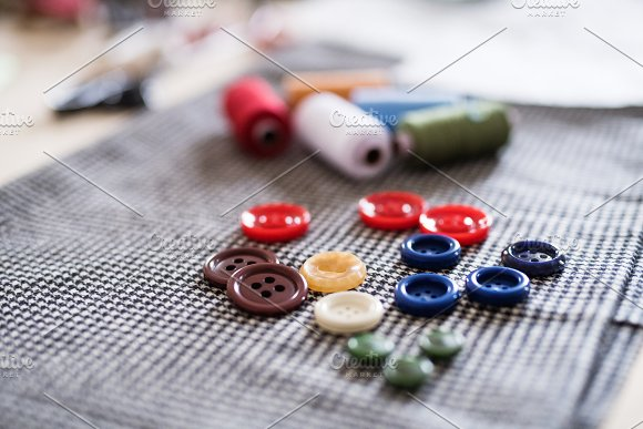 Buttons and thread bobbins on a fabric.