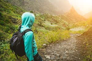 Alone traveler with backpack walking down cobbled trekking trail towards green valley. Sun flares on hoziron. Santo Antao Island, Cape Verde