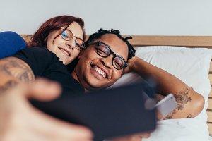 Multiracial couple taking selfie