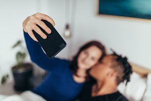 Couple on bed taking selfie