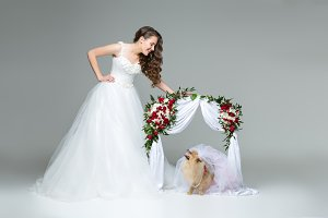 bride girl with dog bride under flower arch