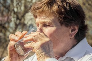 An old woman drinks water.