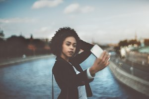 Black girl taking selfie on bridge