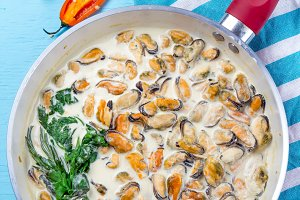 Mussels in milk cream y sauce with aromatic herbs and lemon in red cooking pan. Blue background
