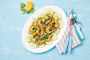 MEXICAN CUISINE. Aguachile de camaron. Prawns aguachile. Shrimps eviche cebiche with cucumber, lemon and purple onion. Top view, blue background.