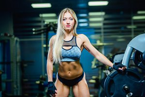 Muscular sexy fitness woman woman relaxing in the gym. Concept of healthy lifestyle. Bodybuilder in the gym