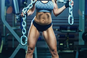 Young sexy woman doing exercises with heavy chain in gym. Classic bodybuilding. Muscular blonde fitness woman doing exercises in the gym. Fitness woman in the gym. Bodybuilder woman in the gym.