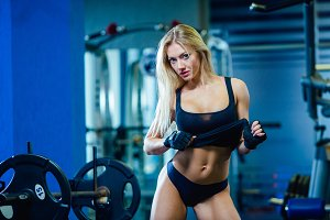 Brutal fitness sexy woman with a muscular in the gym. Sports and fitness - concept of healthy lifestyle. Fitness woman in the gym.