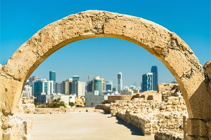 Ancient arch at Bahrain Fort with skyline of Manama. A UNESCO World Heritage Site