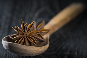 Star anise seeds in a wooden spoon