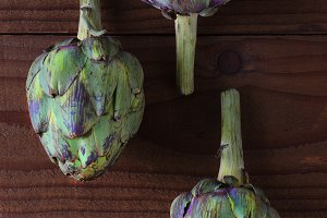 Three Artichokes on Wood Table