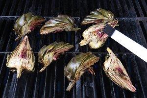 Tongs turning artichoke on grill