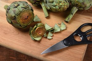 Cutting board with fresh artichokes