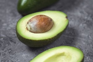 Fresh avocado on a dark table.