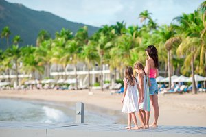 Adorable little girls and young mother on white beach in luxury resort