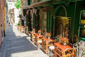 Medieval street with outdoor cafe in the Italian hill town of Genova. The traditional italian medieval historic center in Liguria, Italy