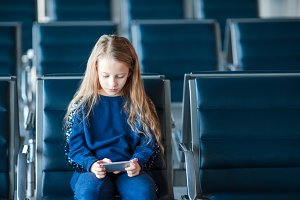 Little adorable girl in airport waiting for boarding playing with laptop