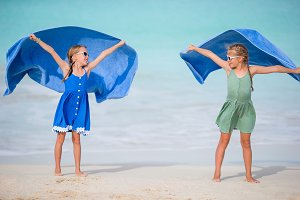 Happy girls having fun running and enjoying vacation on tropical beach with white sand and turquoise ocean water