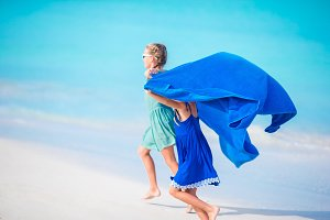 Little girls having fun enjoying vacation on tropical beach with white sand and turquoise ocean water