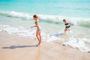 Two little happy girls have a lot of fun at tropical beach playing together at shallow water. Kids splashing.