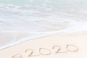2020 year written on white sandy beach