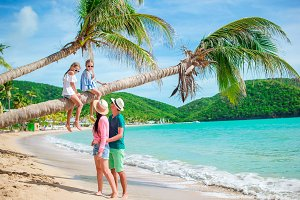 Little girls having fun sitting on the palm tree. Happy family relaxing on tropical beach with white sand and turquoise ocean water