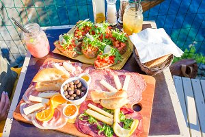 Tasty italian snack. Fresh bruschettes, cheeses and meat on the board in outdoor cafe with amazing view in Manarola, Italy