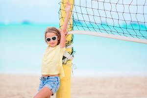 Little adorable girl playing beach volleyball with ball. Sporty kid enjoy beach game outdoors
