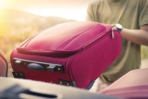 putting the suitcase in the car, lug