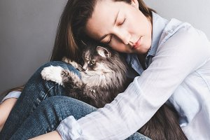 Stylish woman gently hugging kitten
