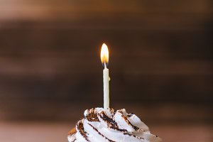 Cream cupcake with one candle.