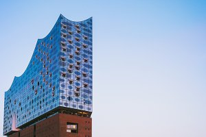 Shape of Elbphilharmonie on bright blue sky with some lilac sunset colors, Hamburg, Germany