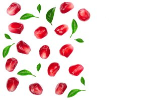 pomegranate seeds decorated with green leaves isolated on white background with copy space for your text. Top view